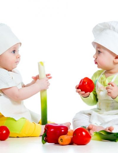 18792402 - babies boy and girl wearing a chef hat with healthy  food vegetables